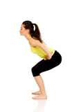 Young woman performs squats. Royalty Free Stock Photography