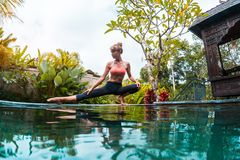 Young woman performs yoga exersices. In the tropical garden near the pool royalty free stock photo