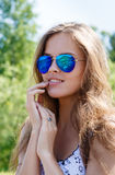 Young woman, the person, sunglasses is reflected the river, roc Royalty Free Stock Photography