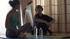 Young woman with personal trainer sitting on the floor on the mats at home. Older and younger women stretching bodies. Healthy lifestyle, recreation, keeping stock footage