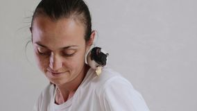 Young woman and pet rat sitting on her shoulder are having a breakfast together. stock video