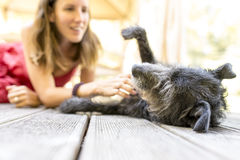 Young woman petting her dog. Young woman petting her black dog on a wooden porch Stock Photo