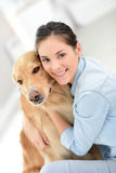 Young woman petting her dog at home Royalty Free Stock Image