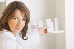 Young woman pharmacist with a bottle of drugs Royalty Free Stock Photography