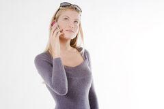Young woman on phone. Beautiful young woman with blond hair on mobile cellphone, isolated on  white Royalty Free Stock Photography
