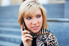 Young woman on the phone. Young blonde woman on the phone against architectural background Royalty Free Stock Photo