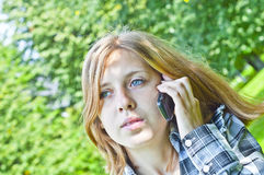 Young woman and phone. Young woman with mobile phone in park Royalty Free Stock Photos