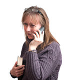 Young woman on phone. A young woman holding a book whilst talking on the phone Royalty Free Stock Images
