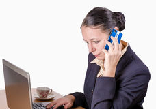 Young woman on phone. Young businesswoman is talking on phone while in front of her computer Royalty Free Stock Photo
