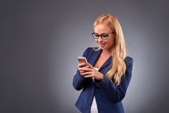 Young woman with a phone. A beautiful young businesswoman in eyeglasses feeling surprised while using her smartphoner stock photography
