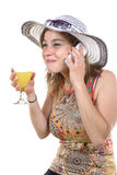 Young woman on the phone and drinking a glass Stock Images