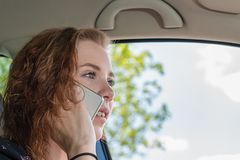 Young woman drives her car and makes a phone call royalty free stock image