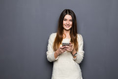 Young woman with phone. On grey background Stock Photo