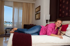 Young woman on the phone in her hotel room royalty free stock image