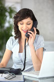 Young woman on phone with laptop Royalty Free Stock Photography