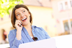 Young woman on the phone with laptop Stock Image