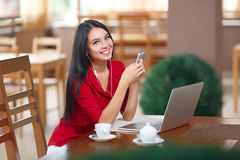 Young woman with phone and laptop sitting in the cafe Stock Images