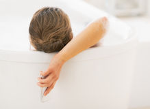 Young woman with phone laying in bathtub Stock Images