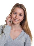 Young woman with phone looking at camera Royalty Free Stock Image