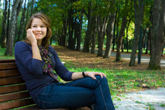 Young woman with phone in park Stock Photo