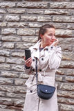 Young woman with a phone... Photo of a young woman, holding a mobile phone (smartphone with large display) in her hand and looking somewhere right (thinking of Stock Images
