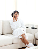 Young woman on phone sitting on the sofa Royalty Free Stock Image