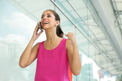 Young Woman On The Phone Smiling For Joy. Portrait of young woman talking on mobile phone, getting good news and exulting for joy Stock Images