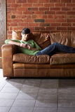 Young woman with phone on sofa Stock Image