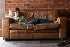 Young woman with phone on sofa Stock Photography