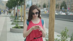 Young woman with phone is spending time on street in summer day. Female in sunglasses goes quickly, then stops, looks around buildings and smartphone screen stock video footage