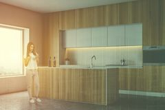Girl with phone in wooden kitchen with bar. Young woman with phone standing in modern kitchen corner with wooden countertops and cupboards and island with built stock photo