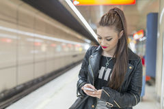 Young woman with phone in subway. Stock Photography