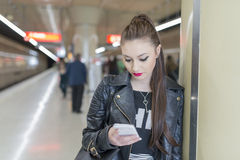 Young woman with phone in subway station. Stock Images