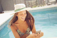 Young woman with phone in swimming pool Stock Photography