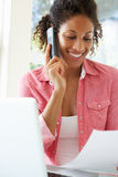 Young Woman On Phone Using Laptop At Home Royalty Free Stock Photo