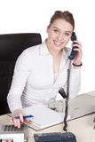 Young woman phones at the desk Stock Image