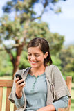 Young woman phoning on the bench Stock Image