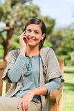 Young woman phoning on the bench Royalty Free Stock Images