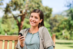Young woman phoning on the bench in the park Stock Photo