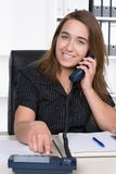 Young woman is phoning in the office Royalty Free Stock Photography