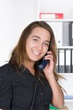Young woman is phoning in the office Stock Photos