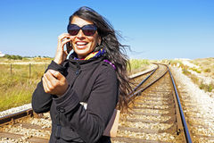 Young woman is phoning at a railroad track Royalty Free Stock Photography