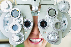 Young woman at phoropter for eye test stock image