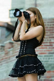 Young fashion woman with photo camera outdoor Stock Photography