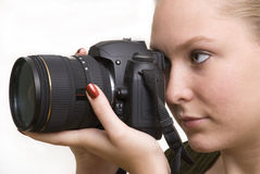 Young Woman Photographer. Young female photographer aiming a reflex camera to take a picture Royalty Free Stock Images