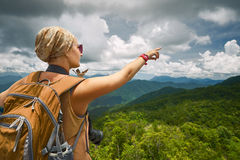 Young woman photographer with backpack standing on top of the mo Royalty Free Stock Photos