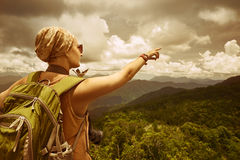 Young woman photographer with backpack standing on top of the mo Stock Images