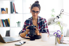 Young woman photographer checking previews on camera in the stud Royalty Free Stock Image