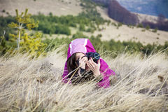 Young woman photographer lying in the mountain taking pictures Stock Image