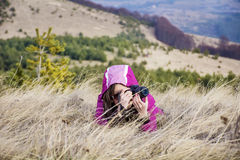 Young woman photographer lying  in the mountain taking pictures Royalty Free Stock Image